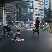 A man with a severe disability begs on a fly-over in Central, Hong Kong's business district, with commuters rushing by on the way to work.  7 million people live on 1,104km square, making it Hong Kong the most vertical city in the world.
