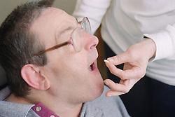 Carer giving man with Cerebral Palsy medication,