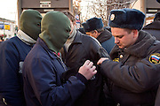 """Moscow, Russia, 04/11/2005..Police search masked demonstrators for weapons during a Russian nationalst demonstration in central Moscow calling for an end to the """"occupation"""" of Russia by illegal immigrants. The demonstration, organised by a variety of extremist nationalist groups led by the Eurasion Youth Union and the Movement Against Illegal Immigration, was held on the first People's Unity Day holiday, which has replaced the old holiday celebrating the Bolshevik Revolution."""