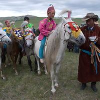 MONGOLIA. A clan elder (carrying ceremonial, fermented mare's milk) leads young, costumed  winners - some who have ridden bareback- after a 20km race at a traditional naadam festival on a remote pass in Arbulag Sum, near Muren in Hovsgol Aimag, Mongolia. The medals on the horses are from earlier races and are a source of great family pride.