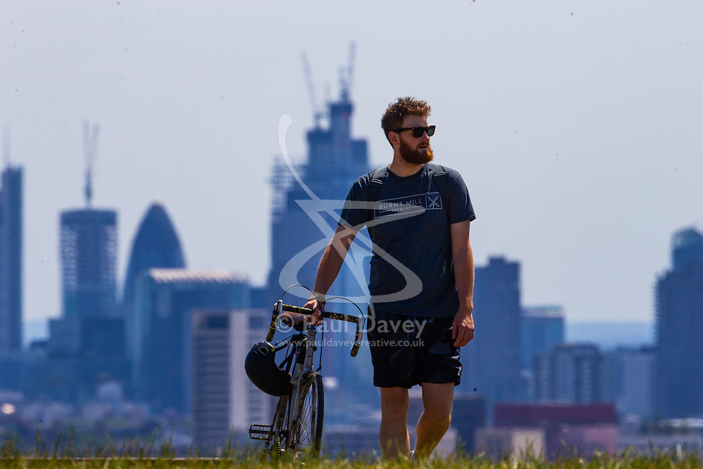 A cyclist takes a break on Parliament Hill on another hot day in London. London, July 03 2018.