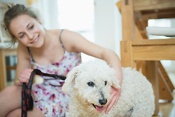 Girl with her dog in living room, smiling