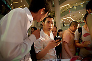 Sales assistant explains mobile phone deals to a customer. Shoppers watch a massive PR promotional push by cell phone company Mororola. Following a stage presentation with models and large screens, the mobile phone giant has staff selling phones to customers as well as fun and giving away gifts by way of mass marketing. Crowds gathered to watch and buy. Xidan is one of the main commercial shopping area in the Xicheng district of Beijing, China. With Joy City as it's centerpiece, a 13-story coplex of western and Chinese shops. This is a shoppers haven as modern consumerism and commerce have a strong grip on Beijing's shop hungry crowds.