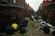 In a rear alleyway between poor terraced housing in Liverpool, England, we see many black bin-bags are left against industrial brick walls awaiting collection during the Merseyside dustmans' strike of 1991. The cobbled alley of these 'back to back' houses are in a poor area, south of the city centre and home to deprived families. The industrial action against the local authority was a health problem for Liverpool during the summer of '91 when streets filled with rubbish. Vermin like rats ran around and public city parks filled with every kind of refuse and garbage. Few of these back-to-backs now exist after being cleared to allow construction of high-rise tower-blocks and flats.