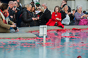 Kitty Comnnolly (9, wearing her dad's medals)and her brother (a cadet) add their poppies to the fountain. A remembrance event in Trafalgar Square included a two minute silence and poppies being placed in the fountains.