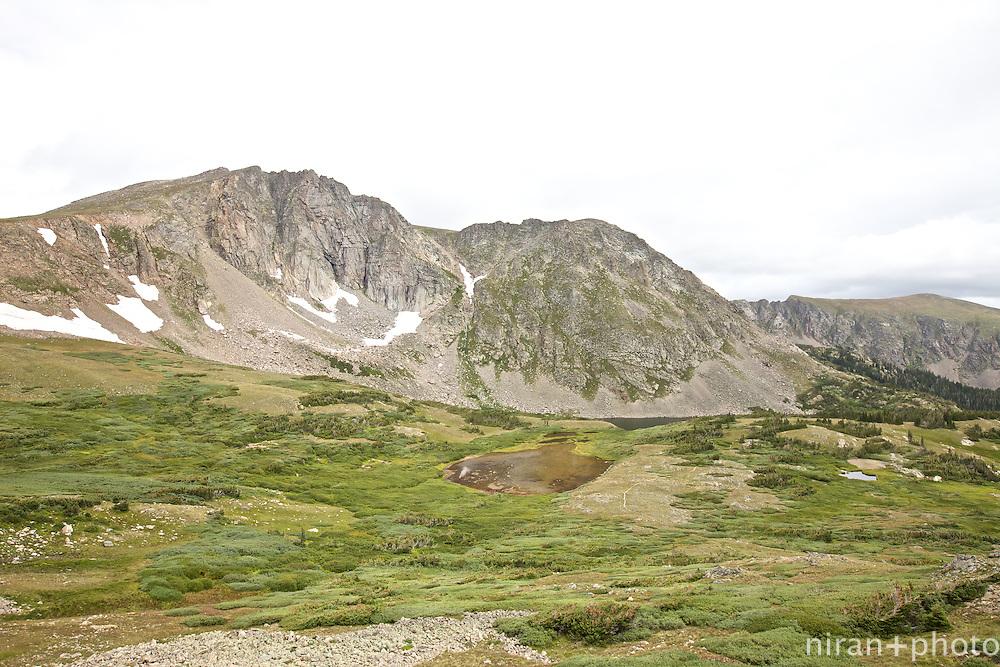 Devil's Thumb Lake nestled by surrounding mountains along the Devil's Thumb Trail.