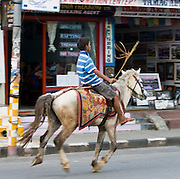 A boy rides a horse down the main street of Lakeside, in Pokhara, Nepal.