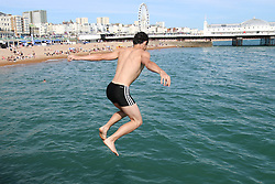 © Licensed to London News Pictures. 17/07/2014. Brighton, UK. Kids jumping in to the sea from the jetty on Brighton beach during the hottest day of the year so far. Temperatures in parts of the south east are expected to hit 28C degrees today. Photo credit : Hugo Michiels/LNP