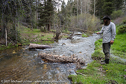Danger Dan Hardick fishing off a trail just outside Red River, NM, USA. Saturday, May 29, 2021. Photography ©2021 Michael Lichter.