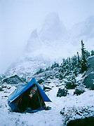 Randi Hirschmann perring from tent on snowy morning in Cirque of the Towers, Warbonnet Peak beyond, Wind River Range, Popo Agie Wilderness, Shoshone National Forest, Wyoming.