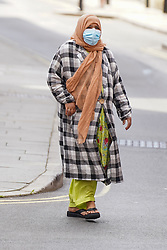 © Licensed to London News Pictures. 13/08/2020. Oldham, UK. A woman wears a face covering as she walks through the streets of Oldham this afternoon.  In recent weeks, the town of Oldham has seen a rapid increase in new coronavirus cases. Photo credit: Ioannis Alexopoulos/LNP