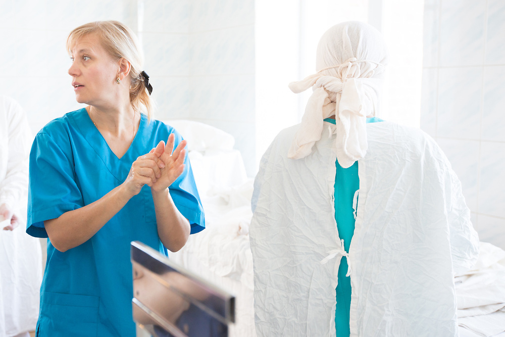 CAPTION: Maxillofacial surgeon Dr Fomenko ensures her hands are thoroughly sanitised, prior to commencing surgery. LOCATION: Volgograd City Hospital #1, Volgograd, Russia. INDIVIDUAL(S) PHOTOGRAPHED: Dr Irena Fomenko (left) and Irina Shukova (right).