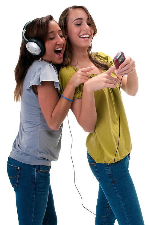 Two young friends listening music and laughing very happy.
