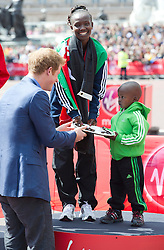 © London News Pictures. 22/04/2012. London, UK. HRH Prince Harry presenting the winners trophy to  Mary Keitany of Kenya and her son  Mary Keitany came first in the elite women's race at the 2012 Virgin London Marathon on April 22, 2012. Photo credit : Ben Cawthra /LNP