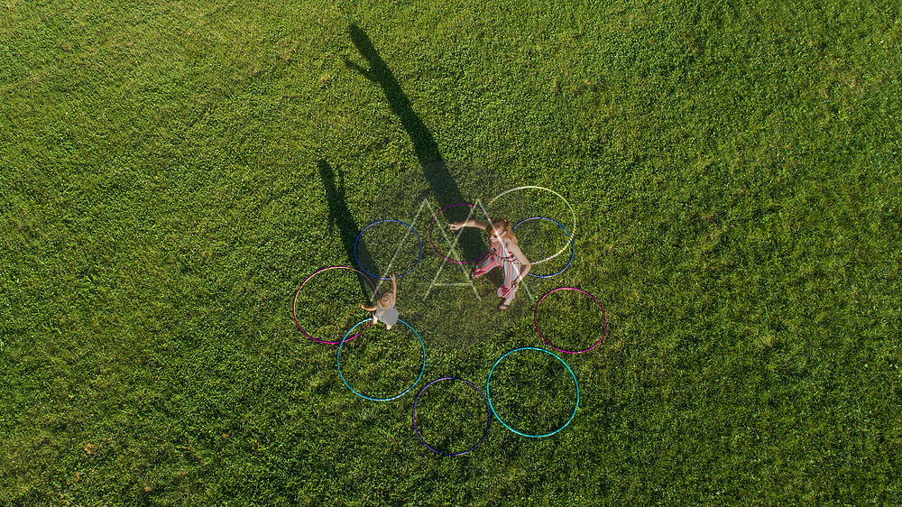 Aerial view of a woman with a kid relaxing on a public park with Hola Hoop in Zagreb downtown, Croatia.