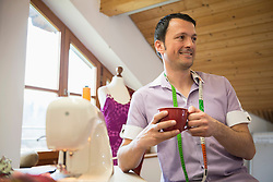 Male dressmaker having a cup of coffee with sewing machine, Bavaria, Germany
