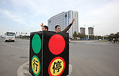 Two Men in a boxed Traffic Light Direct Traffic