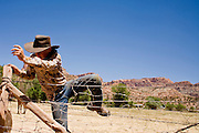 """June 16, 2008 -- COLORADO CITY, AZ: A member of the Jessop family jumps over the fence around their horse corral in Colorado City, AZ. The Jessops are a polygamous family and members of the FLDS. Colorado City and neighboring town of Hildale, UT, are home to the Fundamentalist Church of Jesus Christ of Latter Day Saints (FLDS) which split from the mainstream Church of Jesus Christ of Latter Day Saints (Mormons) after the Mormons banned plural marriage (polygamy) in 1890 so that Utah could gain statehood into the United States. The FLDS Prophet (leader), Warren Jeffs, has been convicted in Utah of """"rape as an accomplice"""" for arranging the marriage of teenage girl to her cousin and is currently on trial for similar, those less serious, charges in Arizona. After Texas child protection authorities raided the Yearning for Zion Ranch, (the FLDS compound in Eldorado, TX) many members of the FLDS community in Colorado City/Hildale fear either Arizona or Utah authorities could raid their homes in the same way. Older members of the community still remember the Short Creek Raid of 1953 when Arizona authorities using National Guard troops, raided the community, arresting the men and placing women and children in """"protective"""" custody. After two years in foster care, the women and children returned to their homes. After the raid, the FLDS Church eliminated any connection to the """"Short Creek raid"""" by renaming their town Colorado City in Arizona and Hildale in Utah.   Photo by Jack Kurtz"""