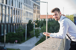 Businessman leaning against railing and holding digital tablet, Munich, Bavaria, Germany