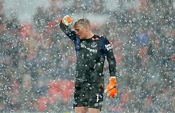Everton goalkeeper Jordan Pickford shelters from the snow during the Premier League match at the bet365 Stadium, Stoke.