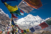 A man stands alone contemplating Annapurna South as prayer flags sway in the wind at Annapurna Base Camp, Himalaya Mountains, Nepal.