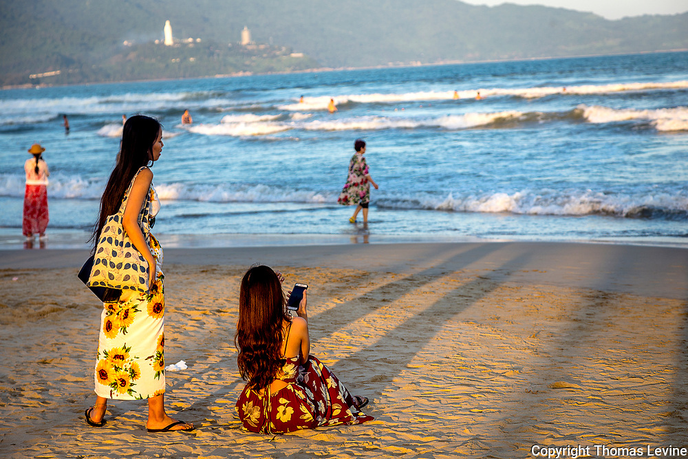 Two Asian girls on the beach at Da Nang with large Buddha across the water.