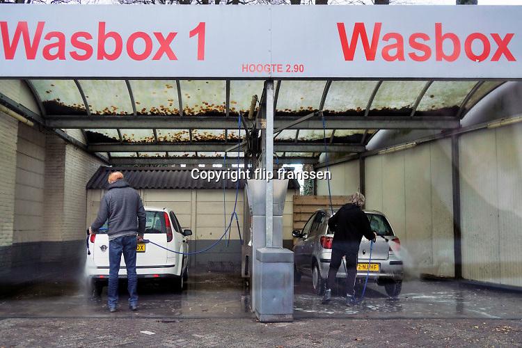 Nederland, Nijmegen, 21-12-2019In een wasbox zijn mensen hun auto aan het afspoelen, wassen, met een hogedrukspuit .Foto: Flip Franssen