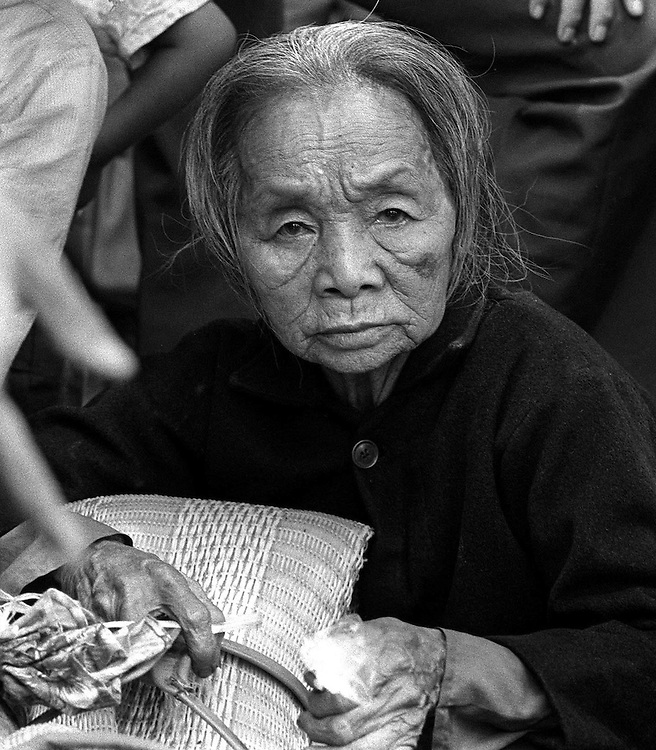 Eldery South Vietnamese refugee waiting patiently for help during the evacuation of Xuan Loc, Vietnam. April 1975. Photographed by Terry Fincher