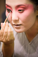 Beijing opera performer applying makeup backstage before a performance in the Zhengyici Peking Opera Theatre in Beijing, China.