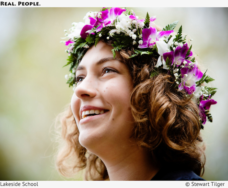 High school senior at graduation ceremony wearing flowers in her hair.