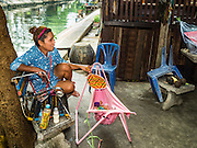 27 AUGUST 2016 - BANGKOK, THAILAND: A woman fans her baby while children sit on the bank of a canal in the Pom Mahakan slum. The Pom Mahakan community is known for fireworks, fighting cocks and bird cages. Mahakan Fort was built in 1783 during the reign of Siamese King Rama I. It was one of 14 fortresses designed to protect Bangkok from foreign invaders. Only two of the forts are still standing, the others have been torn down. A community developed in the fort when people started building houses and moving into it during the reign of King Rama V (1868-1910). The land was expropriated by Bangkok city government in 1992, but the people living in the fort refused to move. In 2004 courts ruled against the residents and said the city could evict them. The city vowed to start the evictions on Sept 3, 2016, but this week Thai Prime Minister Gen. Prayuth Chan-O-Cha, sided with the residents of the fort and said they should be allowed to stay. Residents are hopeful that the city will accede to the wishes of the Prime Minister and let them stay.       PHOTO BY JACK KURTZ