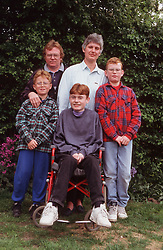 Family group standing together in garden with young son with disability; who is wheelchair user,