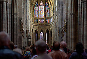 A group of tourists visiting St. Vitus Cathedral in Prague.