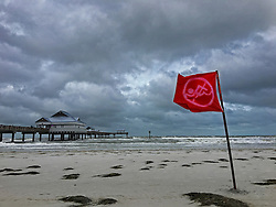 October 7, 2016 - Tampa, Florida, U.S. - JIM DAMASKE   |   Times .A no swimming flag flies on Clearwater Beach which was windy and rough, according to lifeguards, with 35 to 40 miles-per-hour sustained winds and three to five foot seas Friday morning 10/7/2016 from hurricane Matthew which was on the other side of the state. (Credit Image: © Jim Damaske/Tampa Bay Times via ZUMA Wire)