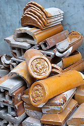 Pile of old ornate ceramic house roof tiles waiting to be recycled in a hutong in an old part of Beijing being  demolished for redevelopment 2009