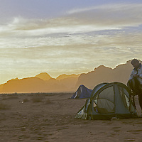 A camper by his tent as sun sets over mountains of Wadi Rum, Jordan.