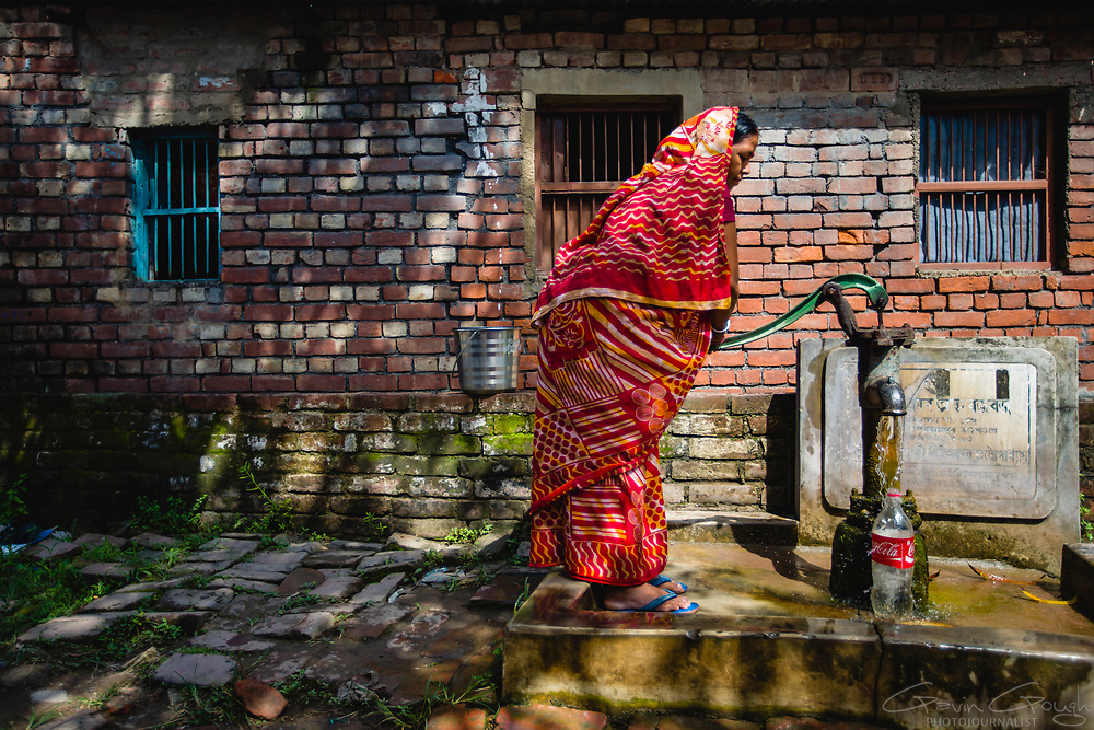 A woman pumping water from a standpipe in the street outside her home, Jote, Shibrampur, Kolkata, India