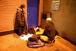 Homeless couple sleeping rough in the inner city streets; settling down for the night,