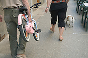 man carrying a children bicycle