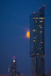 "© Licensed to London News Pictures . 23/07/2013 . Manchester , UK . A blood red moon low over the skyline of Manchester , as seen tonight (23rd July 2013 ) with Manchester's iconic Beetham Tower in the foreground . The phenomenon can be caused by dust and pollution in the atmosphere and is most notable when the moon is low on the horizon as its light passes through a larger amount of atmosphere , which scatters blue light more than red . Biblical mythology makes several references to a red moon including , from Joel 2:31 , "" The sun shall be turned to darkness, and the moon to blood, before the great and awesome day of the Lord comes"" . Photo credit : Joel Goodman/LNP"