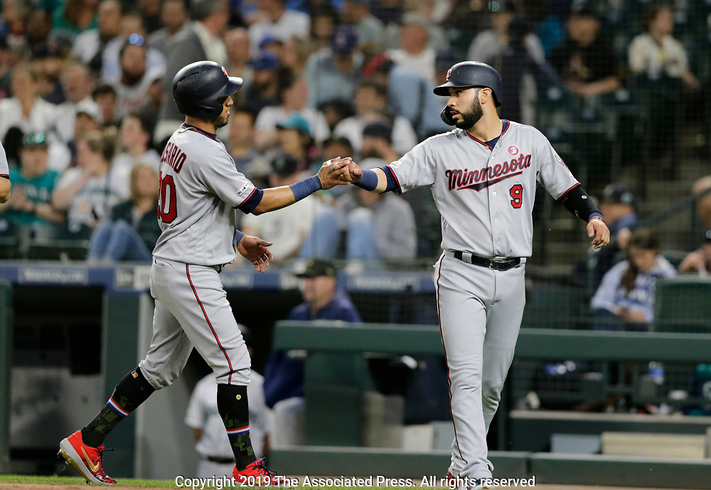 Minnesota Twins' Eddie Rosario, left, and Marwin Gonzalez celebrate after scoring on a double hit by C.J. Cron against the Seattle Mariners during a baseball game, Saturday, May 18, 2019, in Seattle. (AP Photo/John Froschauer)