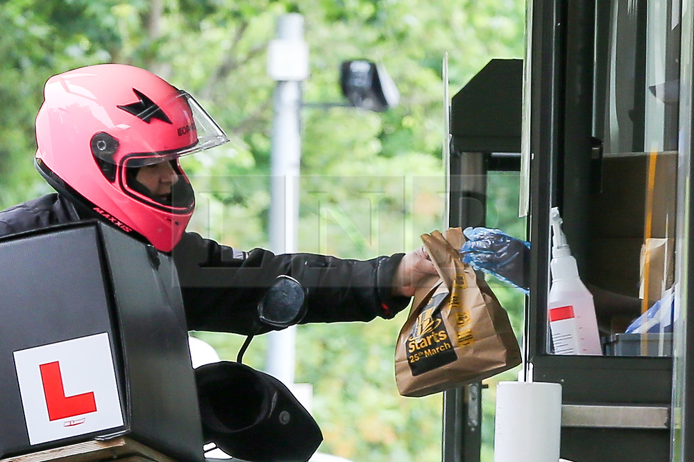© Licensed to London News Pictures. 04/06/2020. London, UK. A staff member wearing plastic gloves hands a meal bag to a delivery driver at McDonald's Drive Thru in north London. McDonald's Drive Thru opens in Haringey after lockdown restrictions are relaxed. Photo credit: Dinendra Haria/LNP