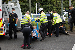 Godstone, UK. 13th September, 2021. Police officers arrest an Insulate Britain climate activist who had been blocking a slip road from the M25, causing a long tailback on the motorway, as part of a new campaign intended to push the UK government to make significant legislative change to start lowering emissions. The activists, who wrote to Prime Minister Boris Johnson on 13th August, are demanding that the government immediately promises both to fully fund and ensure the insulation of all social housing in Britain by 2025 and to produce within four months a legally binding national plan to fully fund and ensure the full low-energy and low-carbon whole-house retrofit, with no externalised costs, of all homes in Britain by 2030 as part of a just transition to full decarbonisation of all parts of society and the economy.