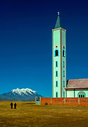 A Catholic church spire rises above Mount Illimani and two men on the windblown Antiplano of El Alto, Bolivia.  The church and many others, were builit by a German missionary.  El Alto is one of the fastest growing cities  in South America and sits above the city of La Paz.