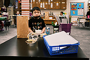 17 FEBRUARY 2021 - DES MOINES, IOWA: A kindergarten student eats his breakfast in the classroom at Walnut Street School in downtown Des Moines. To reduce crowding and improve social distancing the school is serving meals in the classrooms. Des Moines Public Schools (DMPS) opened to in person education this week after teaching most of the 2020-2021 school year either remotely or with a hybrid/remote learning model. The district has ended its hybrid model. The Governor of Iowa has aggressively pushed schools to return to in person education, going so far as to threaten to withhold funds from districts that don't return to in person classes. DMPS, the largest school district in Iowa, has resisted the Governor's push because Polk County, IA, has been a Coronavirus/COVID-19 hotspot with positivity rates well above 10 percent. The district was recently able to vaccinate many teachers and positivity rates have fallen to 9 percent, making it safer to reopen schools.      PHOTO BY JACK KURTZ