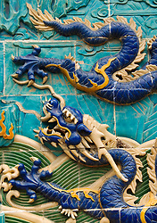 Detail of ceramic tiled dragon on historic Nine Dragon Wall in Beihai Park in Beijing China