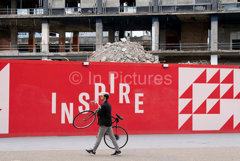 A Londoner and the changing urban landscape of the former Elephant & Castle shopping centre which is being demolished and redeveloped in south London, on 22nd June 2021, in London, England. The much-criticised architecture of the Elephant & Castle Shopping Centre was opened in 1965, built on the bomb damaged site of the former Elephant & Castle Estate, originally constructed in 1898. The centre was home to restaurants, clothing retailers, fast food businesses and clubs where south Londoners socialised and met lifelong partners.
