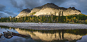 Sunrise illuminates Mount Kidd and reflects in Kananaskis River, in the Kananaskis Range of the Canadian Rockies, Alberta. Access the Mt Kidd Interpretive Trail from Mt Kidd RV Park in Kananaskis Country, which is a park system west of Calgary. This panorama was stitched from 9 overlapping photos.