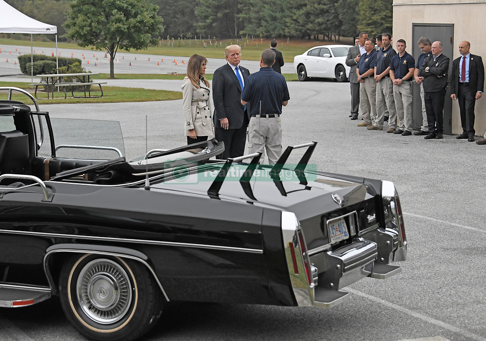 An unidentified United States Secret Service agent speaks with US President Donald J. Trump and first lady Melania Trump as they tour the US Secret Service James J. Rowley Training Center in Beltsville, Maryland on Friday, October 13, 2017.  In the foreground is the car that was used to evacuate then-US President Ronald Reagan from a golf course in Augusta, Georgia on October 22, 1983 when an armed man crashed through the gate of the golf course and demanded to speak to the President.  <br /> Credit: Ron Sachs / Pool via CNP