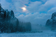Moon over mist in snow-covered Yosemite Valley at dawn, Yosemite National Park, California